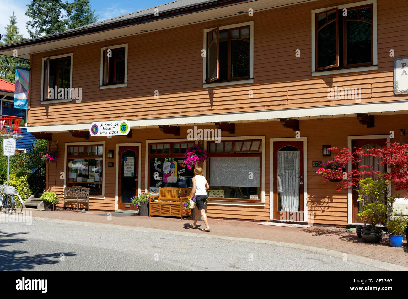 Woman walking by a colorful wooden building at Artisan Square on Bowen island, British Columbia, Canada - Stock Image