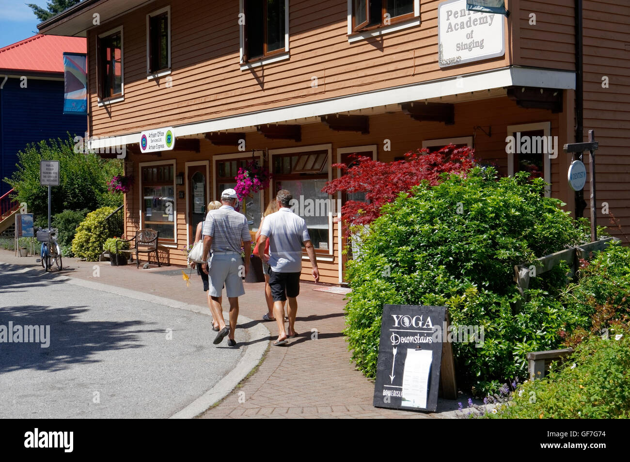 Tourists walking by a colorful building at Artisan Square on Bowen island, British Columbia, Canada - Stock Image
