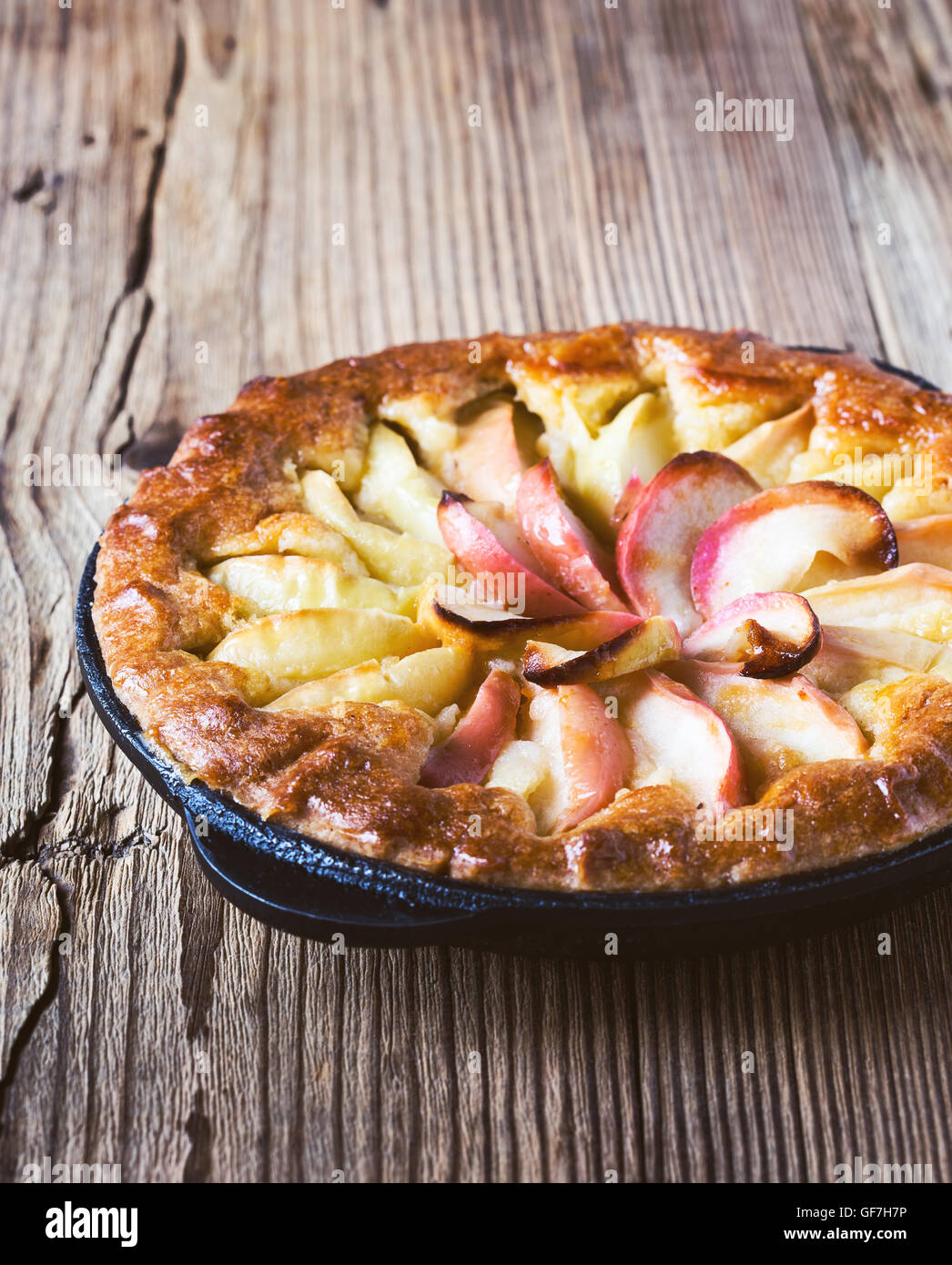Homemade apple pie cooked in a frying pan and ripe apples on rustic wooden table - Stock Image