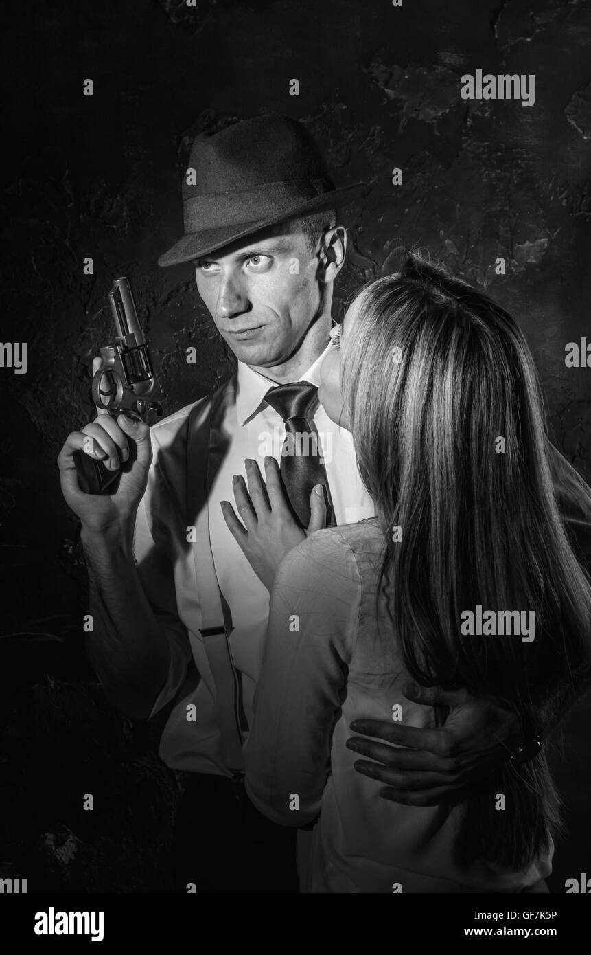 A detective with a gun and his beautiful woman leaning on him. Studio shot. Noir style. Black and white photography - Stock Image