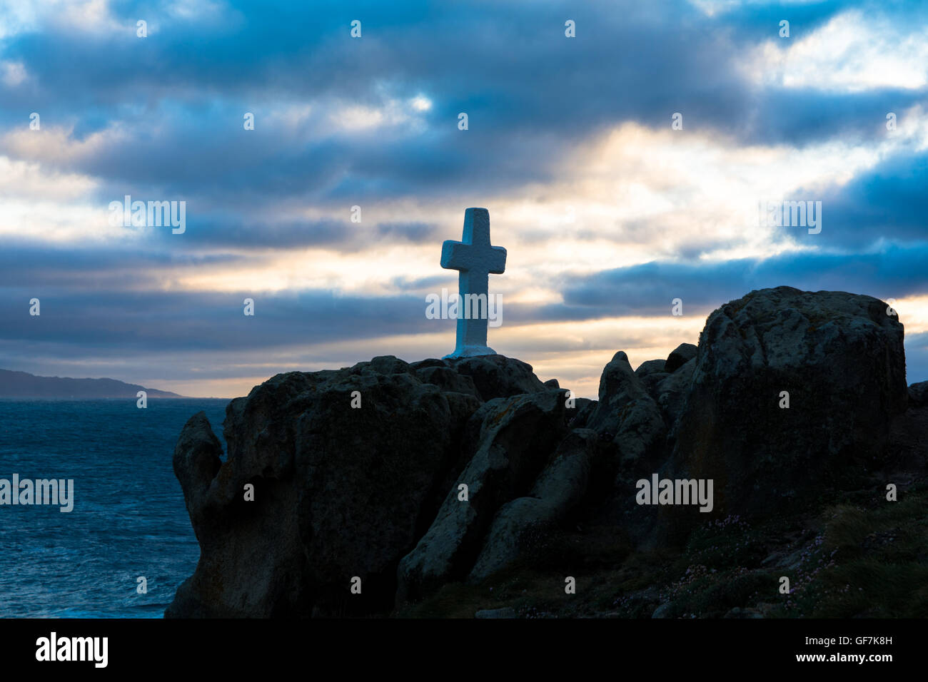 Cross On Shore Against Cloudy Sky - Stock Image