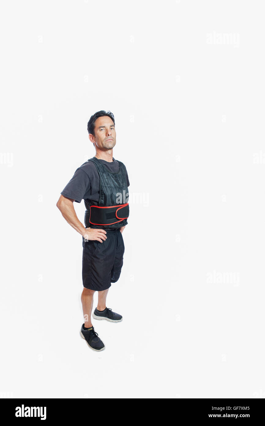 Middle age man tired from heavy weighted vest. - Stock Image