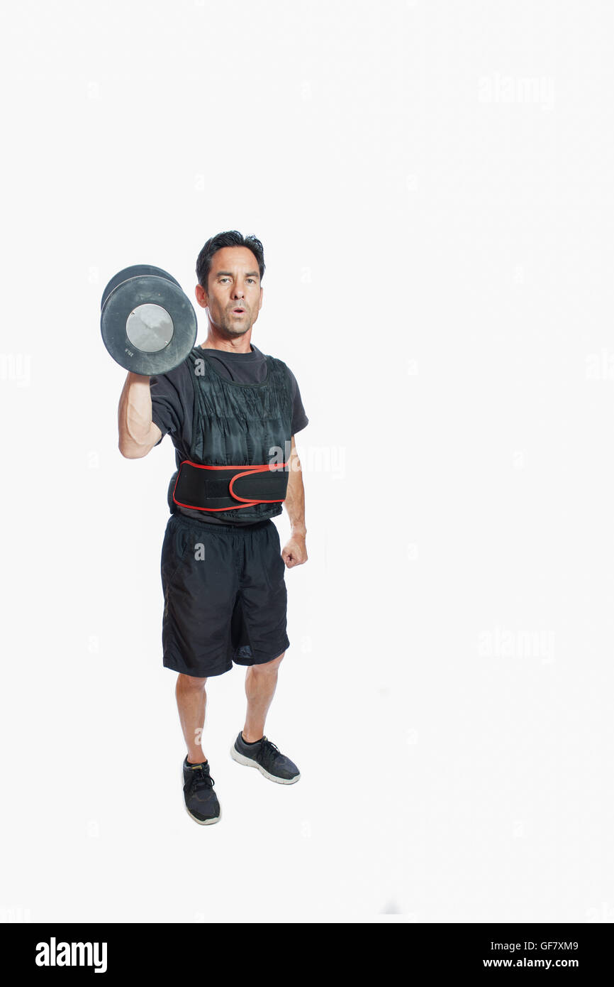Middle age man holding dumbbell with weighted vest. - Stock Image