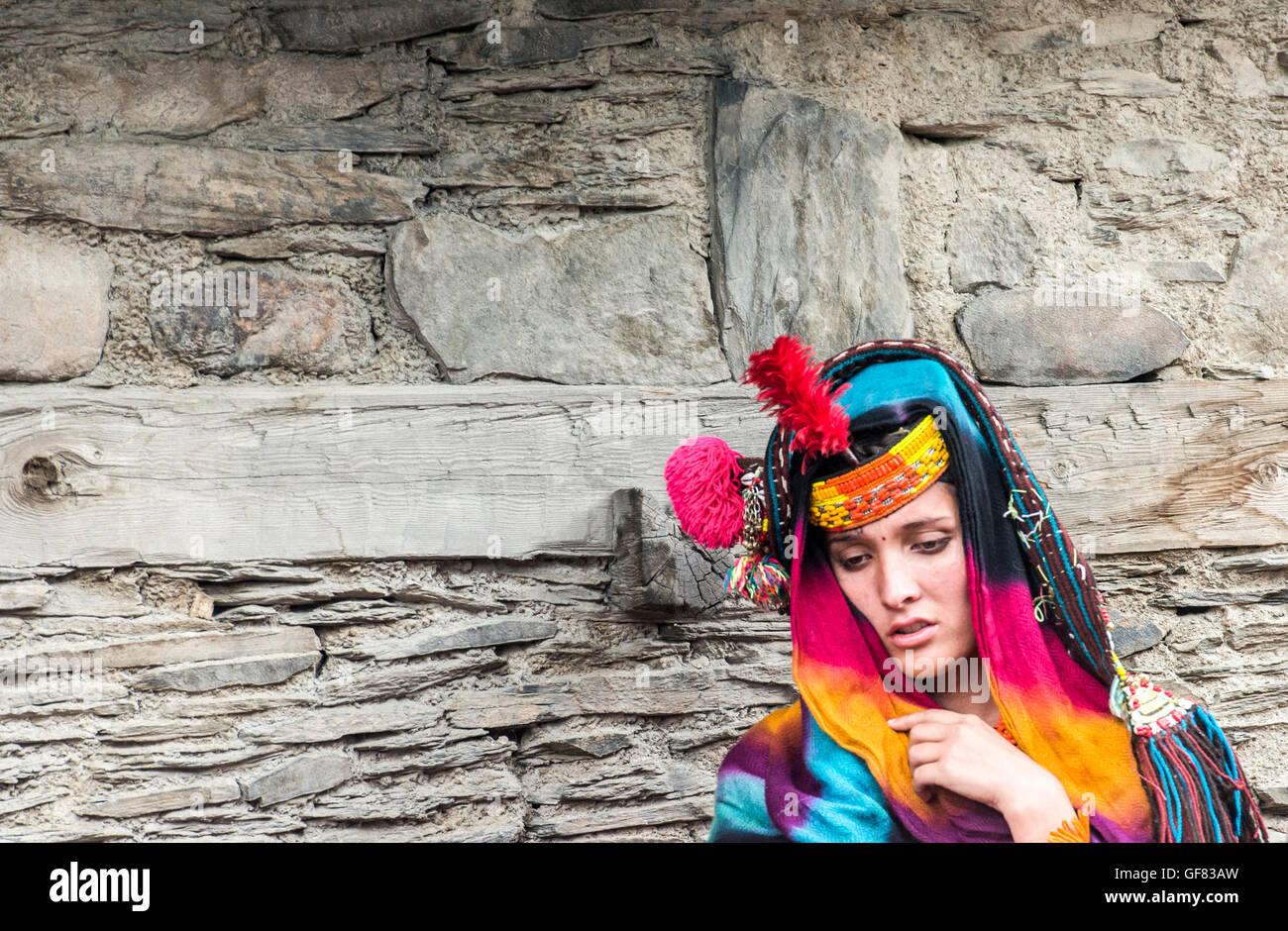 Kalash woman wearing traditional headdress, bead necklaces and embroidered black dress - Stock Image