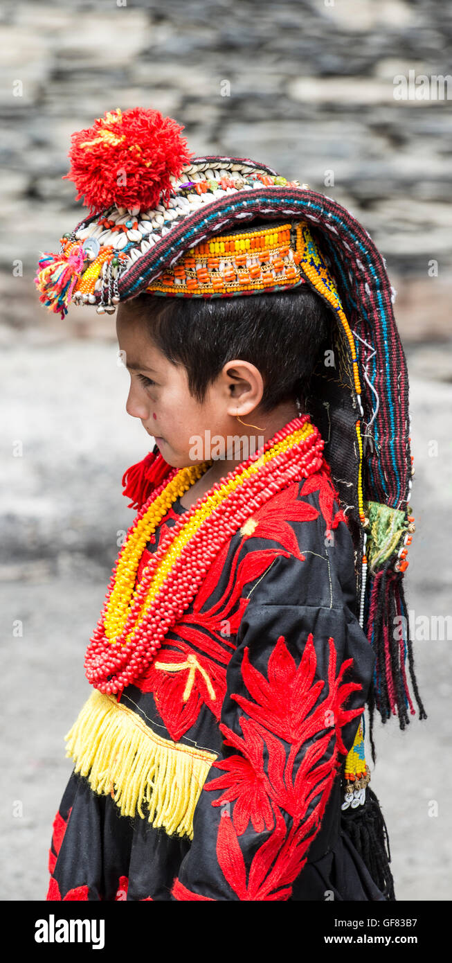 Kalash girl wearing a traditional headdress decorated with cowrie shells and a black embroidered dress - Stock Image