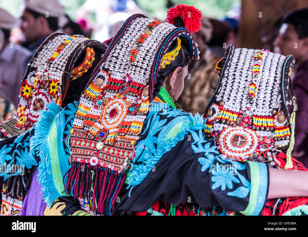Kalash women show off their traditional headdresses decorated with cowrie shells. The are wearing embroidered dresses. - Stock Image
