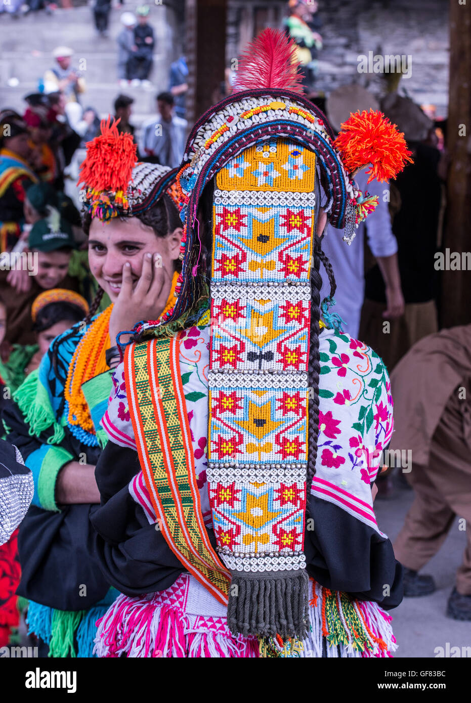Kalash woman wearing a traditional Kalash dress and beaded headdress. Over the beaded headress is a cowrie decorated - Stock Image