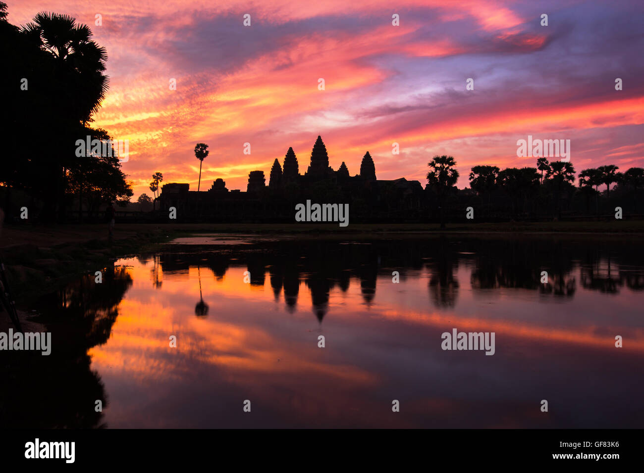 Angkor Wat temple at dramatic sunrise reflecting in water - Stock Image
