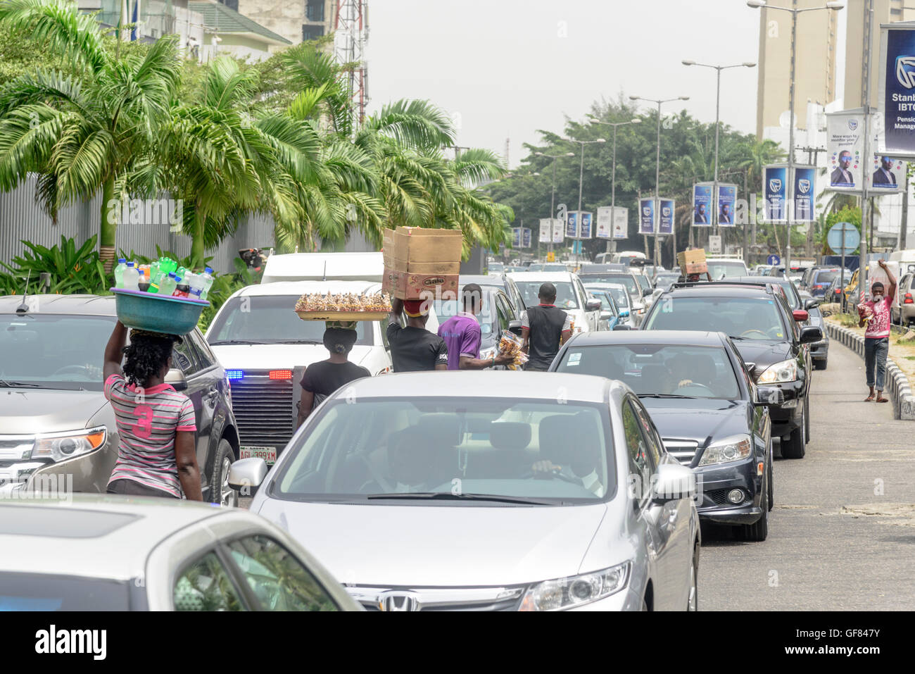 Street hawkers ply their wares in traffic, Victoria Island, Lagos, Nigeria, West Africa - Stock Image