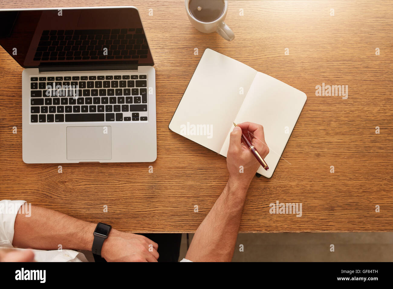 Close up of man writing notes in personal notebook with a laptop and cup of coffee on table. - Stock Image