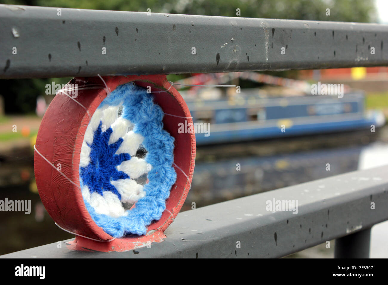 A Crochet canal wheel and bunting attached to a foot bridge over the Leeds and Liverpool canal in Blackburn Lancashire. - Stock Image