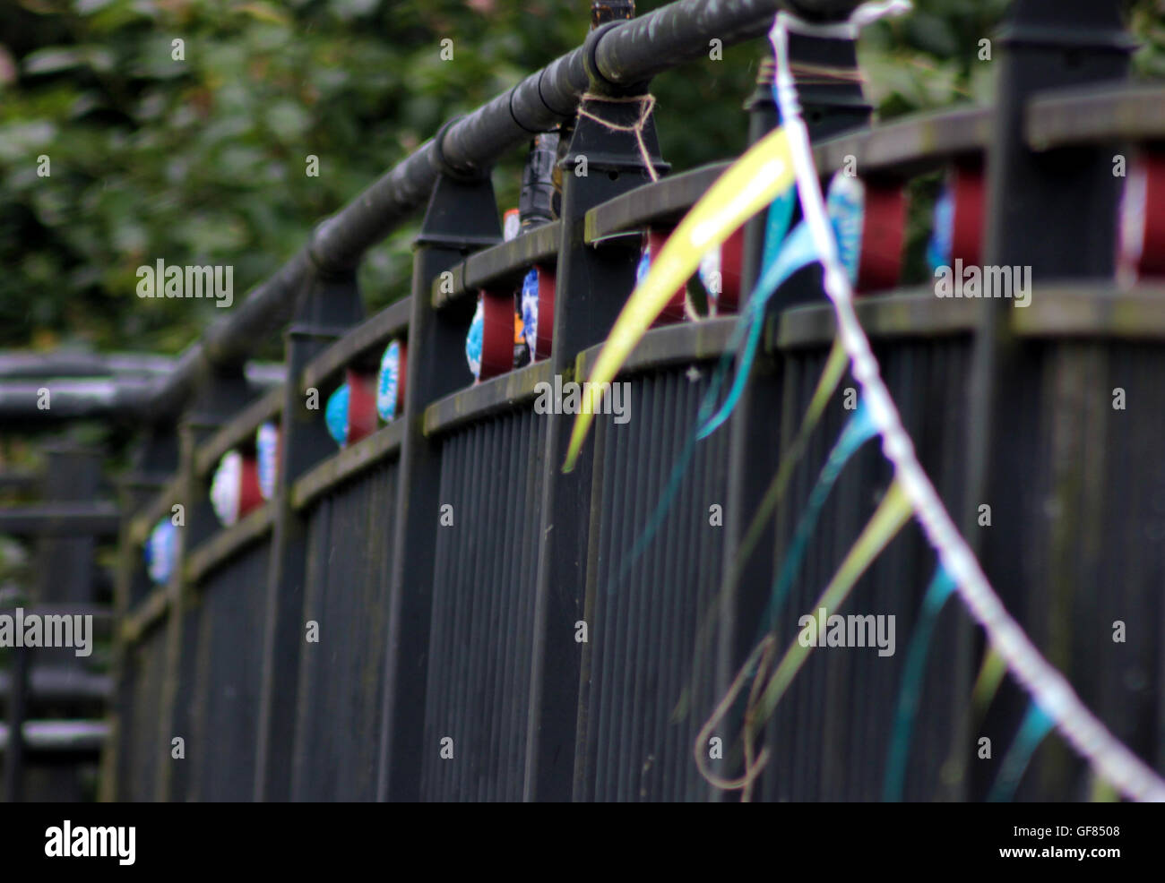 Crochet canal wheels and bunting attached to a foot bridge over the Leeds and Liverpool canal in Blackburn Lancashire. - Stock Image