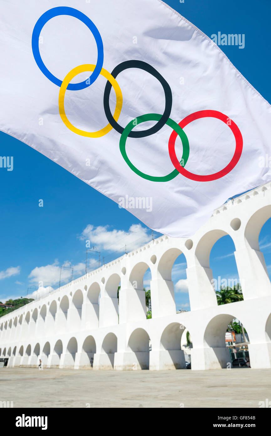RIO DE JANEIRO - MARCH 6, 2015: An Olympic flag flies in the plaza above the famous Lapa Arches landmark. - Stock Image