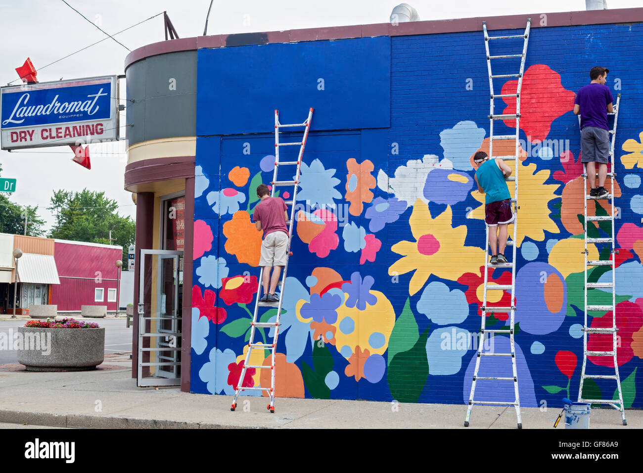 Detroit, Michigan - Youth paint the wall of a laundromat in the Morningside neighborhood. - Stock Image