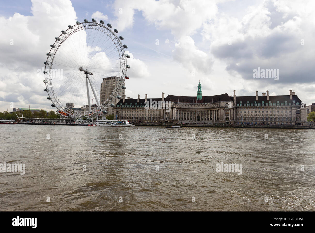The London Eye ferris wheel and the old Greater London Council building on the south bank of the River Thames, London - Stock Image