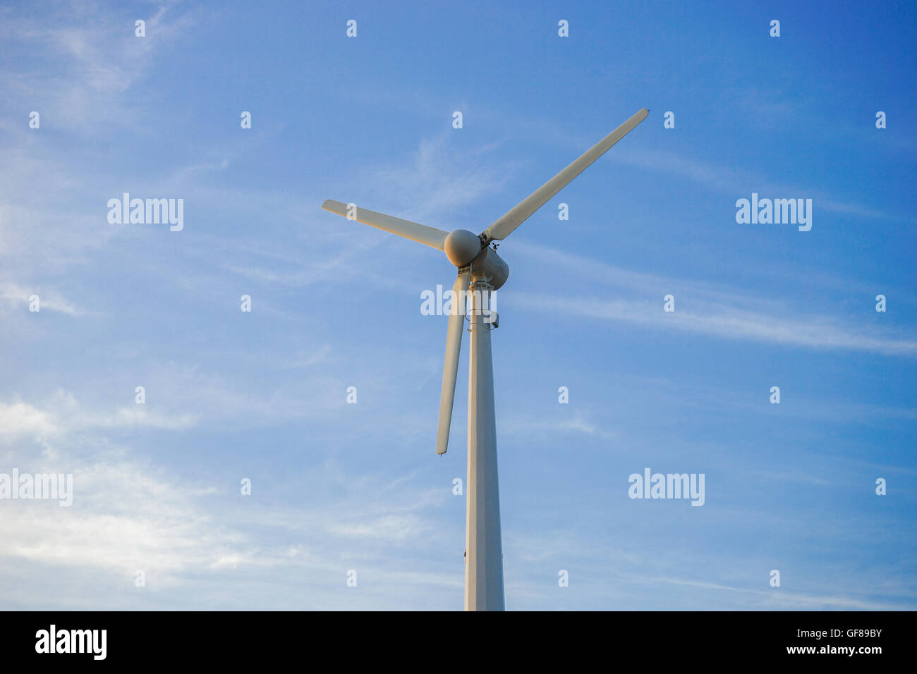 wind turbine against partly cloudy blue sky - Stock Image