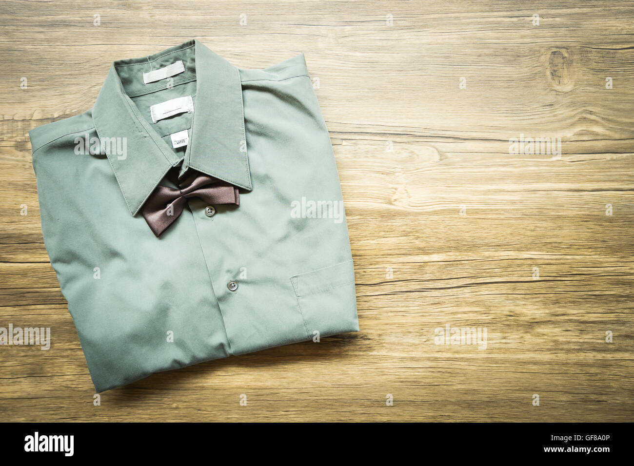 Top view Men's outfits with green shirt and tie on old wood table Stock Photo