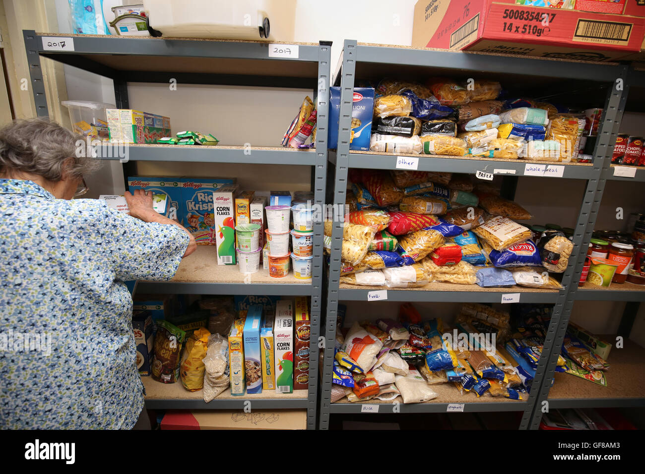 Woman volunteer stacking shelves of a foodbank with provisions - Stock Image