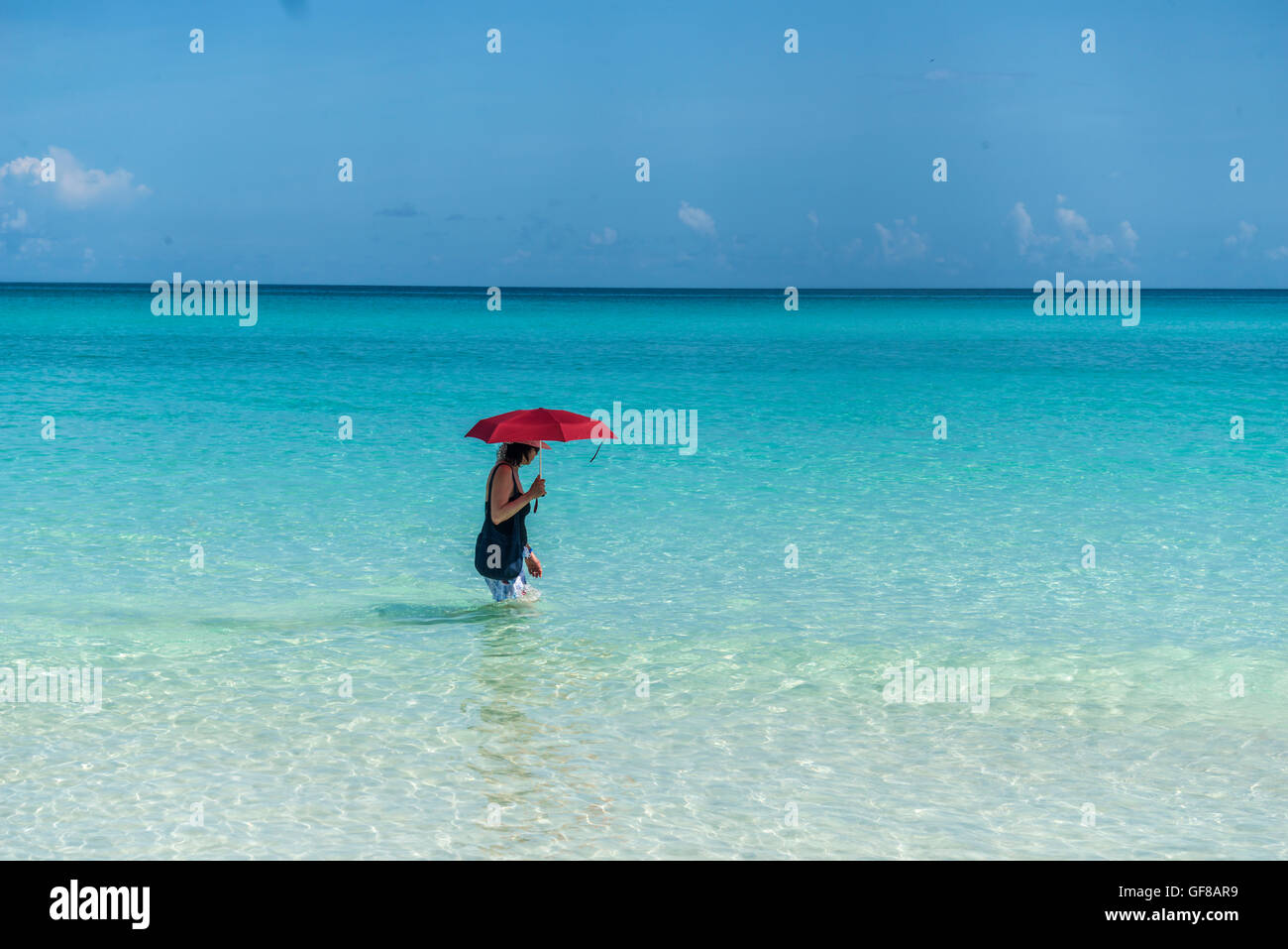 woman walking into the sea water with red umbrella in the Caribbean - Stock Image