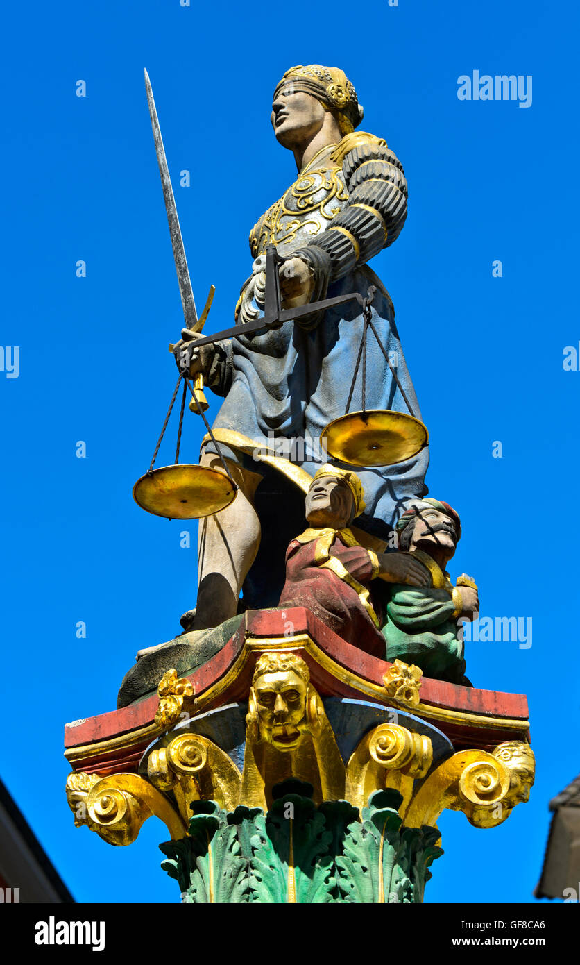 Sculpture of Justitia blindfolded and holding balance scales and a sword on the Fountain of Justice, Neuchatel, - Stock Image