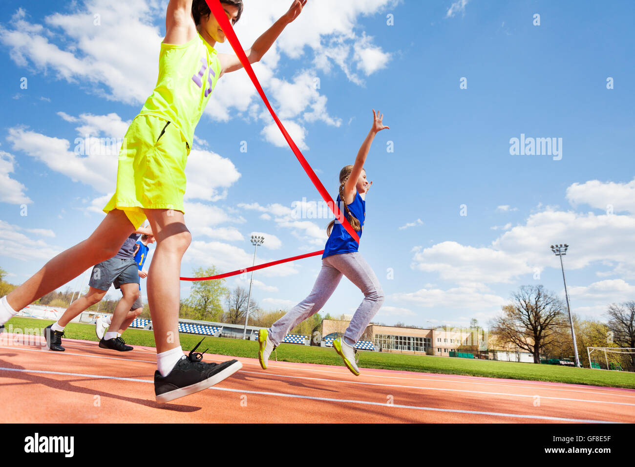 Happy girl crossing finish line on the racetrack - Stock Image