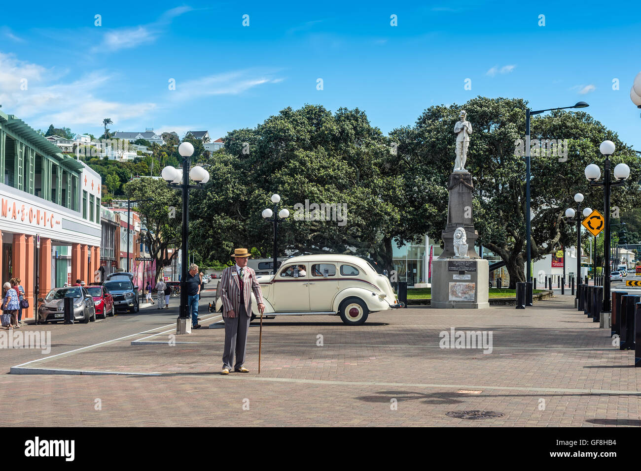 Elderly man 1930s dressed and vintage motorcar on the Marine Parade in the art deco town of Napier - Stock Image