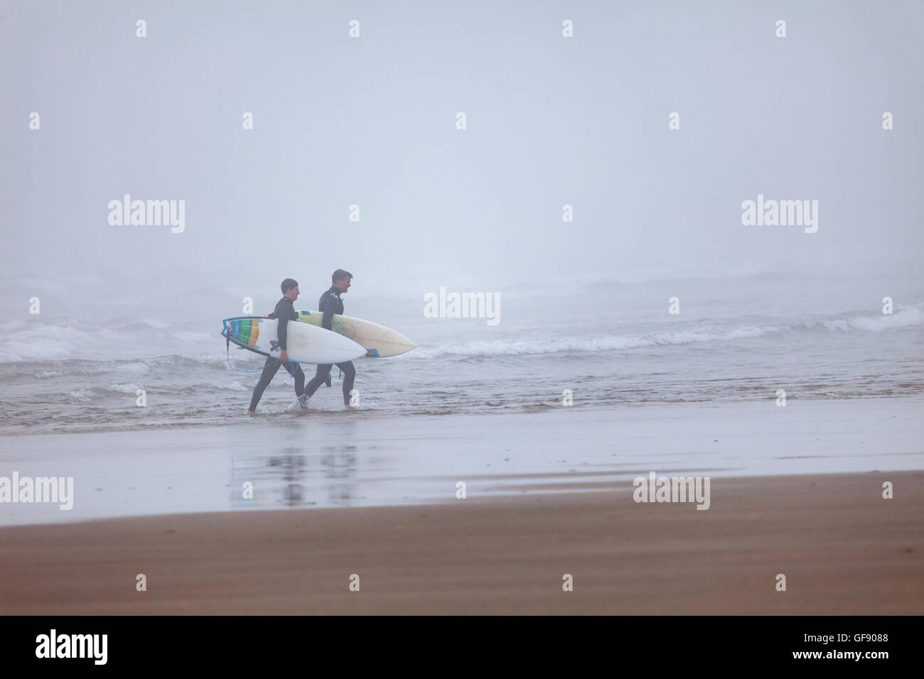 Two cornish surfers returning from the surf at Whitsand Bay located in Cornwall, England, UK as the mist rolls in. Stock Photo