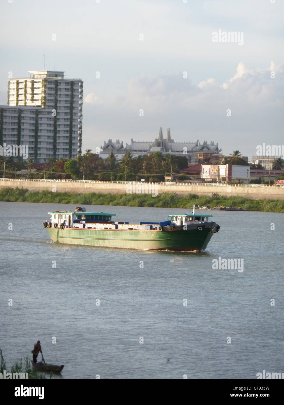 Boat going down the Mekong River...very hot day on the promenade in Phnom Penh. Many boats use this riverway - Stock Image