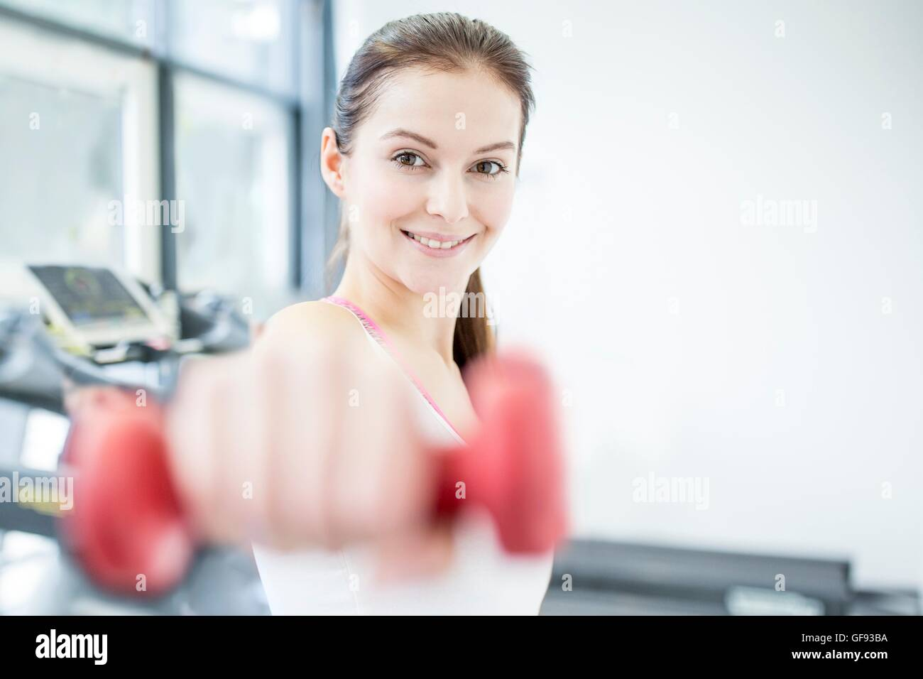 PROPERTY RELEASED. MODEL RELEASED. Smiling young woman working out with dumbbell in gym, portrait. - Stock Image