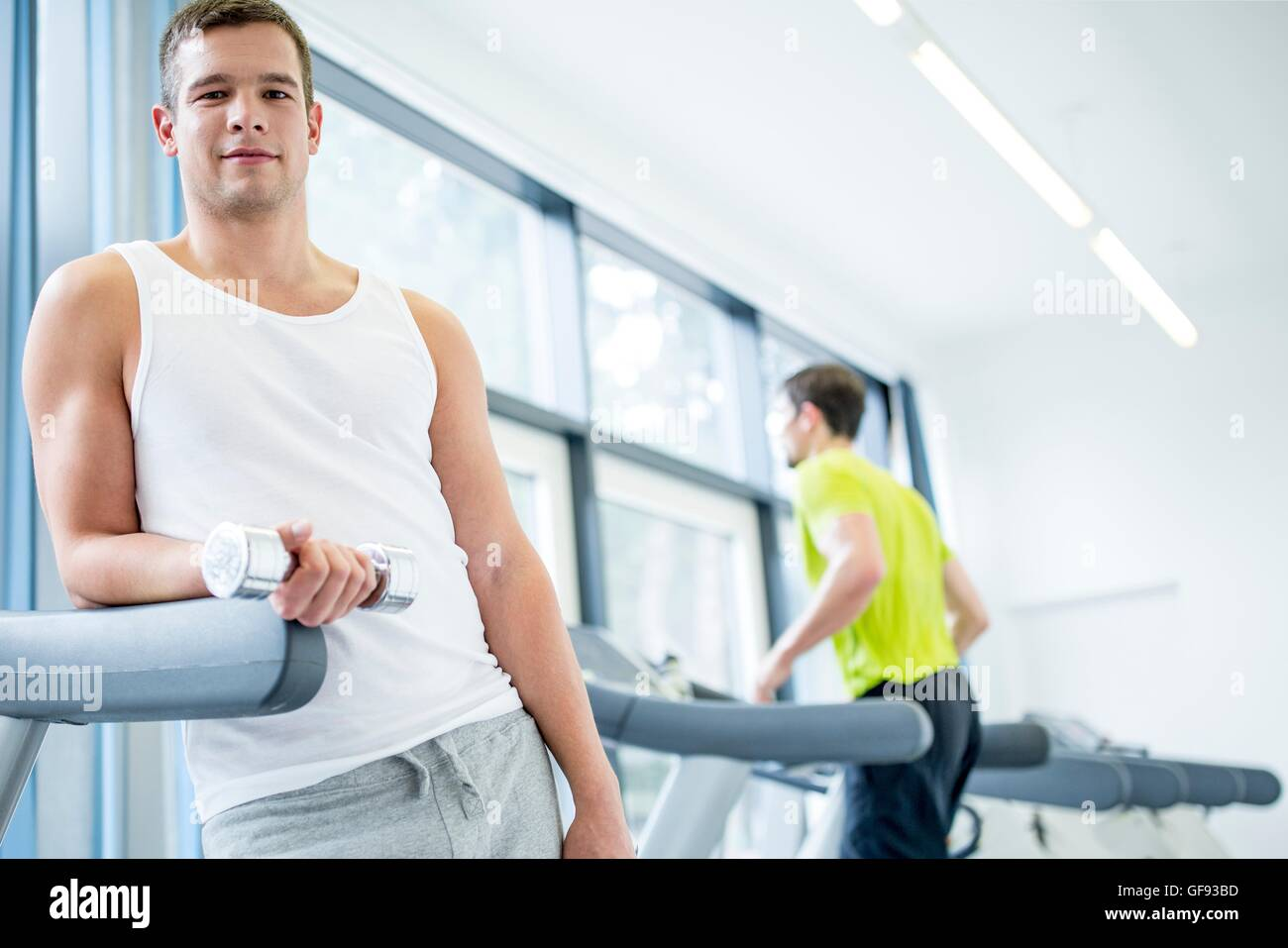 PROPERTY RELEASED. MODEL RELEASED. Portrait of young man holding dumbbells while leaning on treadmill. - Stock Image