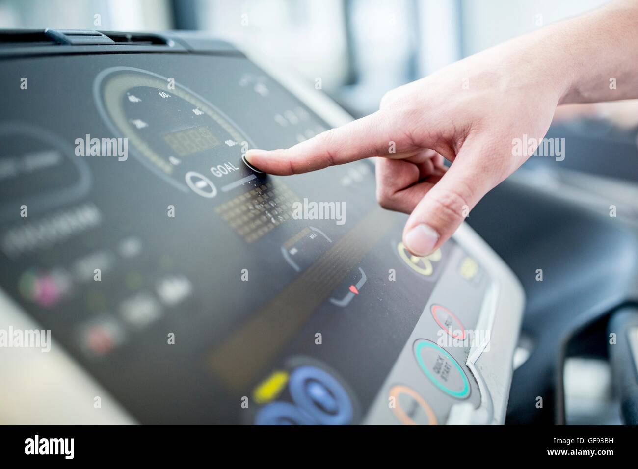 PROPERTY RELEASED. Man pushing control panel button of exercise machine, close-up. - Stock Image