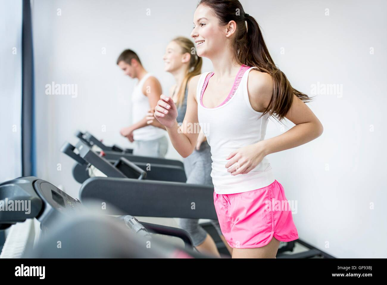 PROPERTY RELEASED. MODEL RELEASED. Young man and women running on exercise machines in gym. - Stock Image