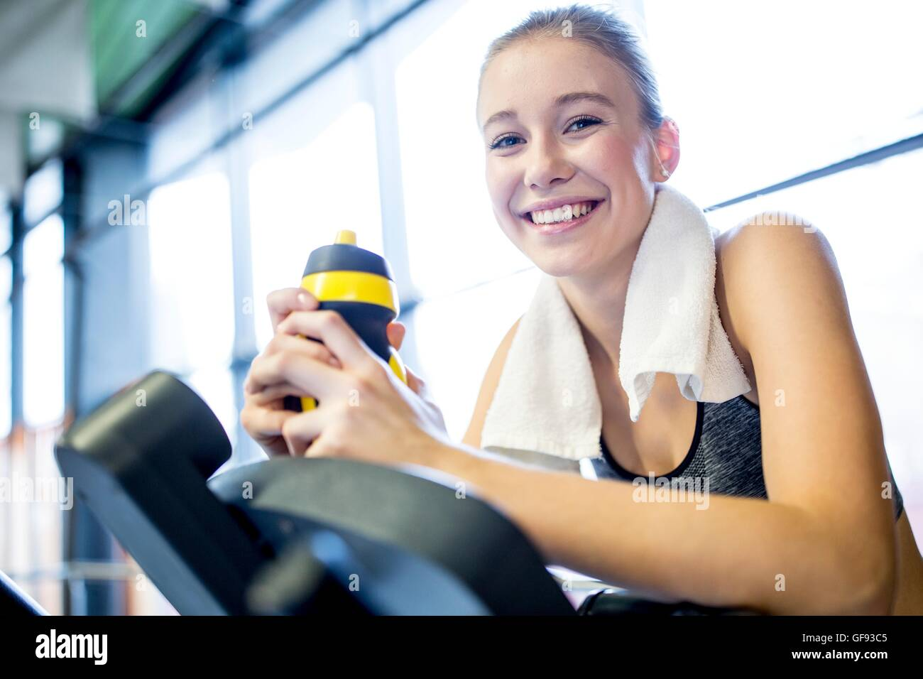 PROPERTY RELEASED. MODEL RELEASED. Young woman holding water bottle while working out in gym, smiling, portrait. - Stock Image