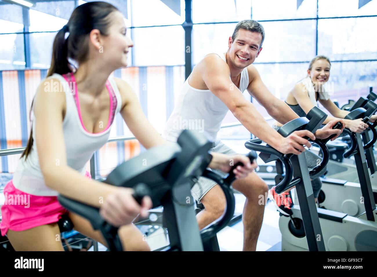 PROPERTY RELEASED. MODEL RELEASED. Young men and women working out on exercise machines in gym, smiling. - Stock Image