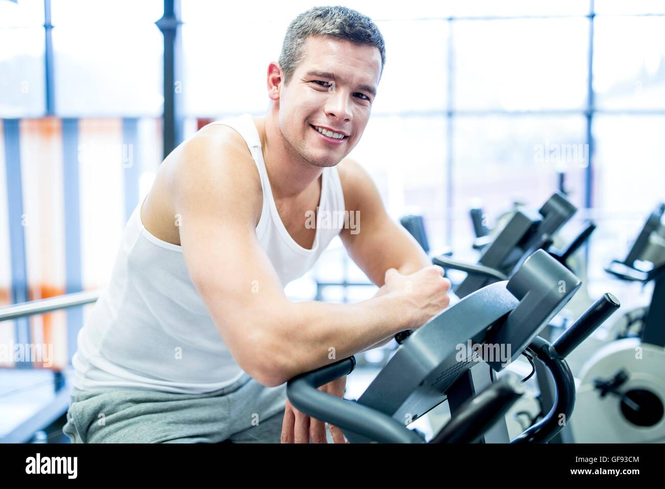 PROPERTY RELEASED. MODEL RELEASED. Portrait of young man resting while work out in gym, smiling. - Stock Image