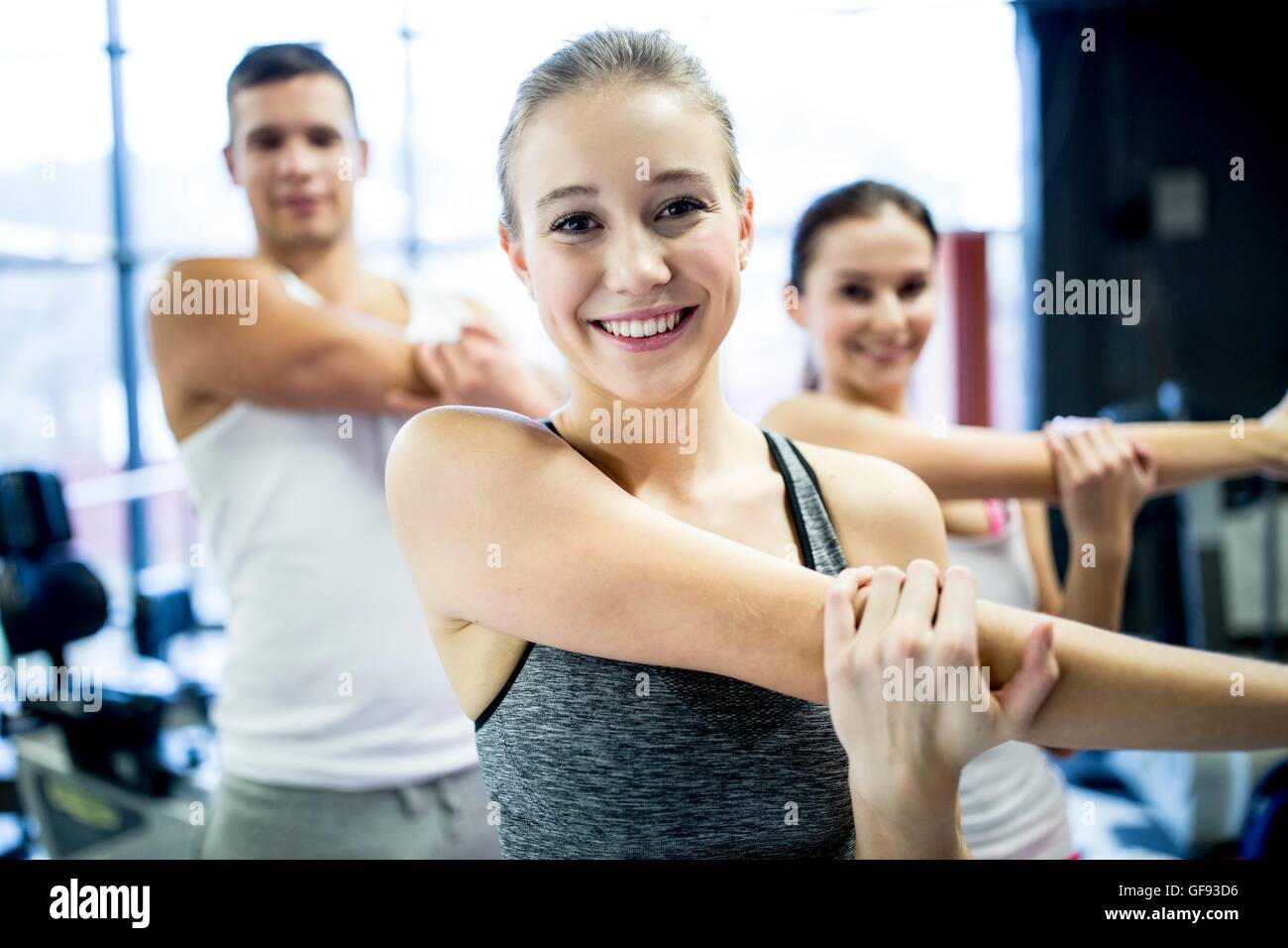 PROPERTY RELEASED. MODEL RELEASED. Young man and women doing warm up exercise in gym. - Stock Image