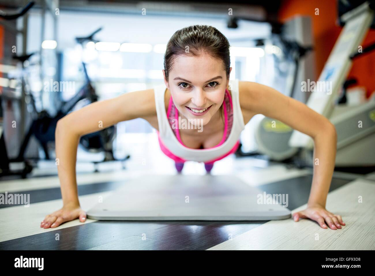PROPERTY RELEASED. MODEL RELEASED. Portrait of young woman doing press-ups in gym. - Stock Image