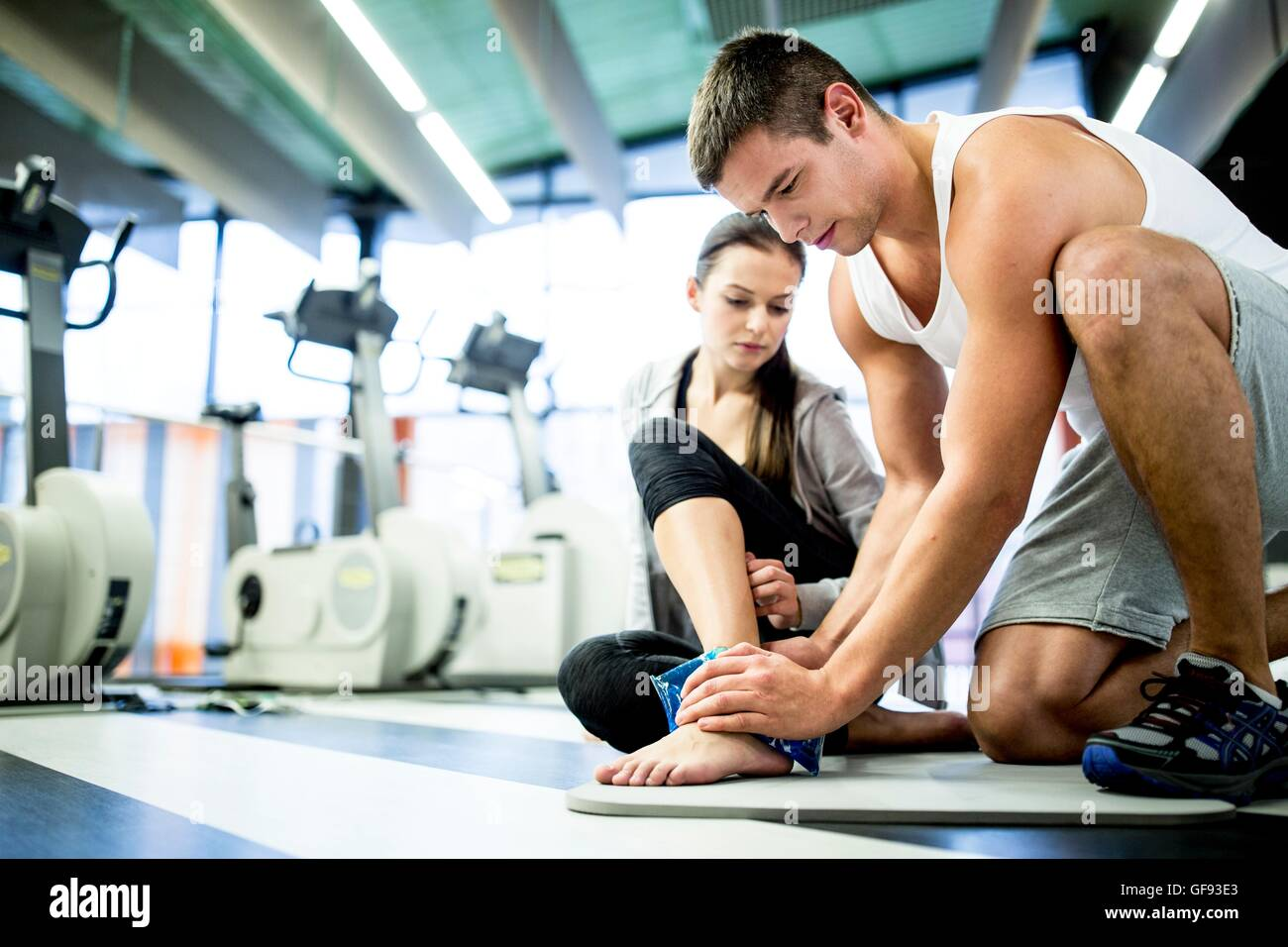 PROPERTY RELEASED. MODEL RELEASED. Young man applying ice pack on young woman's ankle in gym. - Stock Image