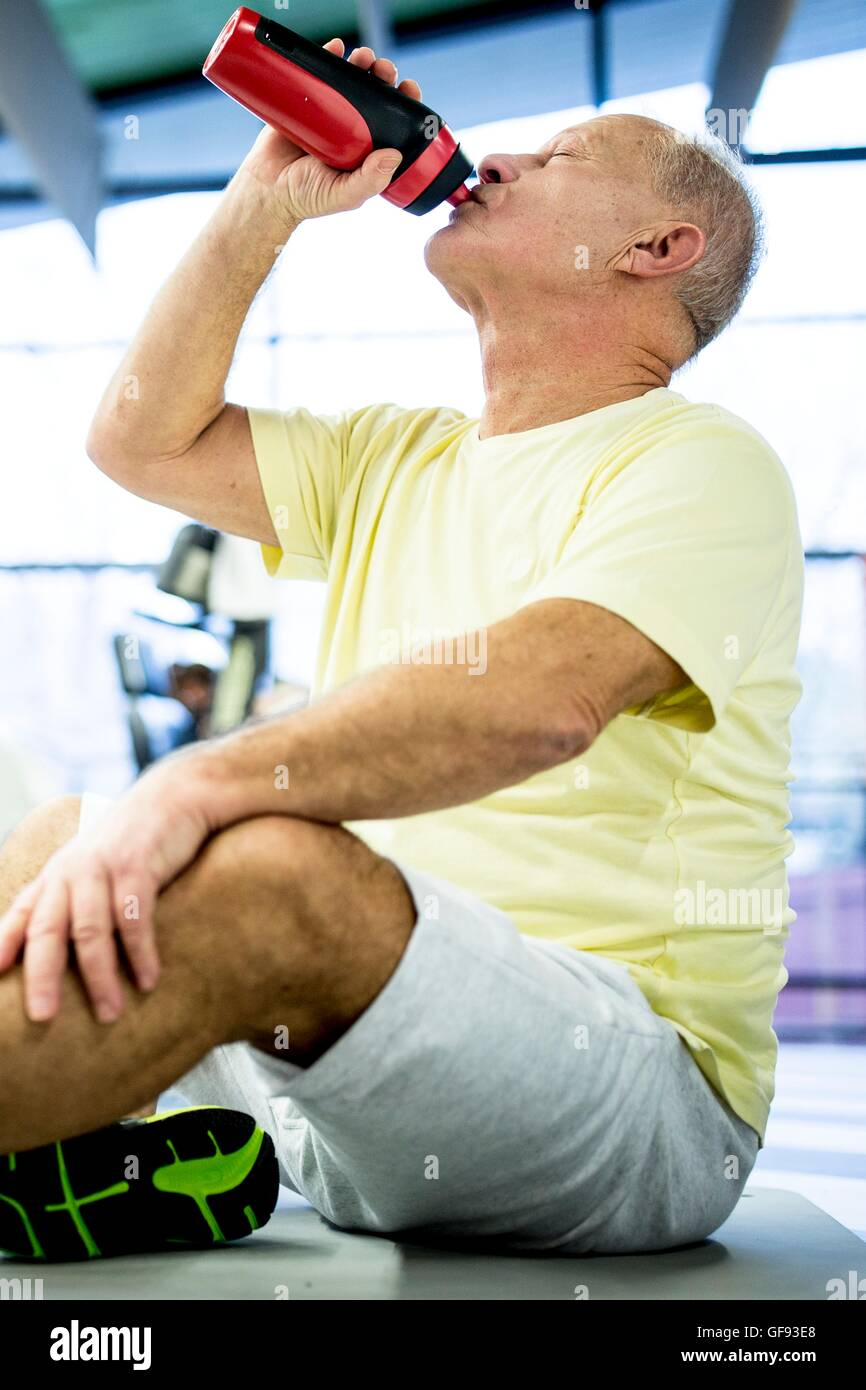 PROPERTY RELEASED. MODEL RELEASED. Senior man sitting and drinking water from water bottle in gym. - Stock Image