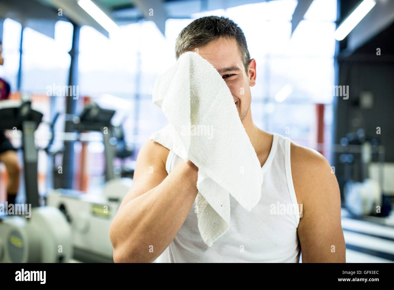 PROPERTY RELEASED. MODEL RELEASED. Portrait young man wiping his sweat with towel after exercising in gym. - Stock Image