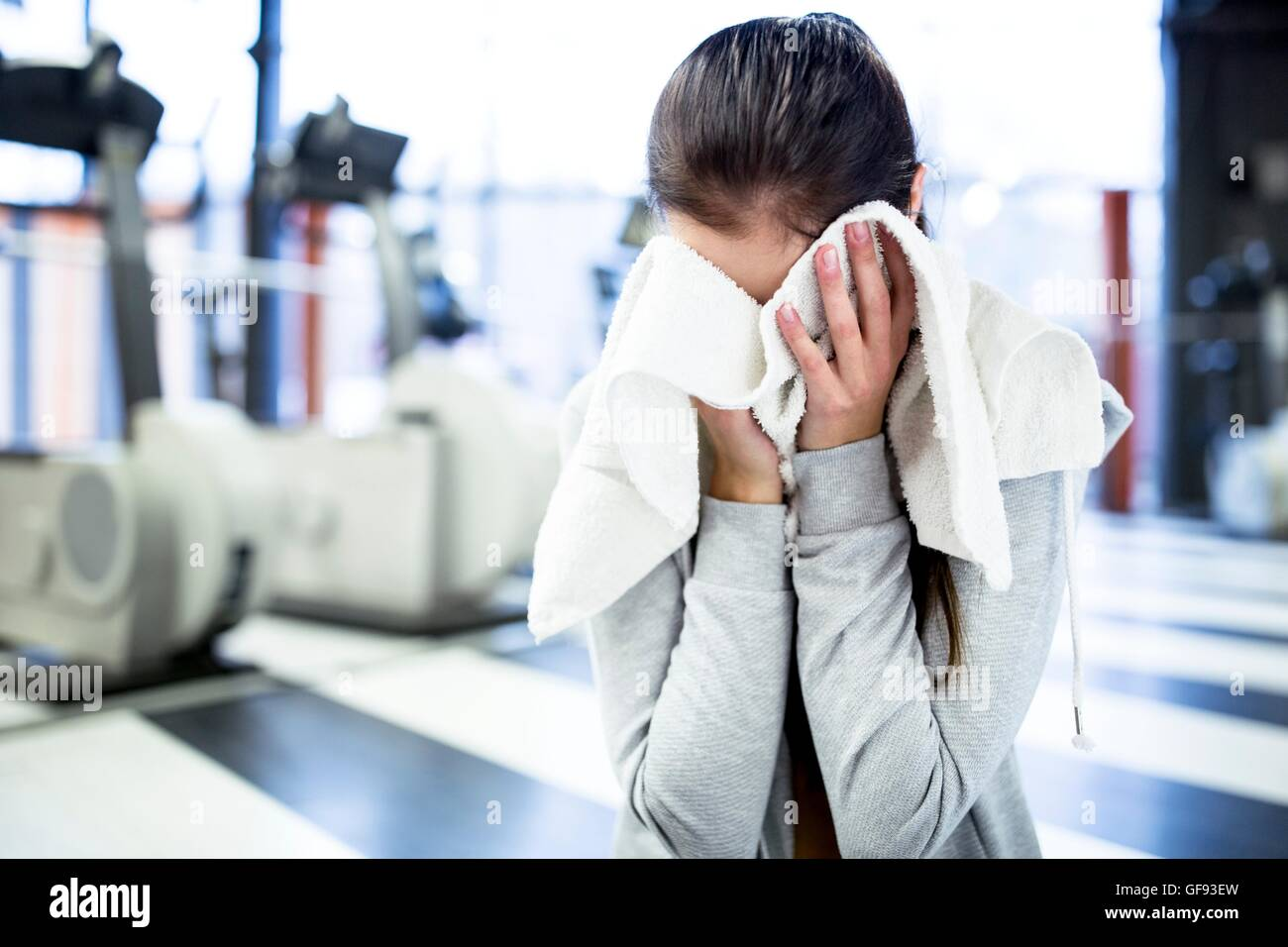 PROPERTY RELEASED. MODEL RELEASED. Cute young woman wiping her sweat after workout in gym. - Stock Image