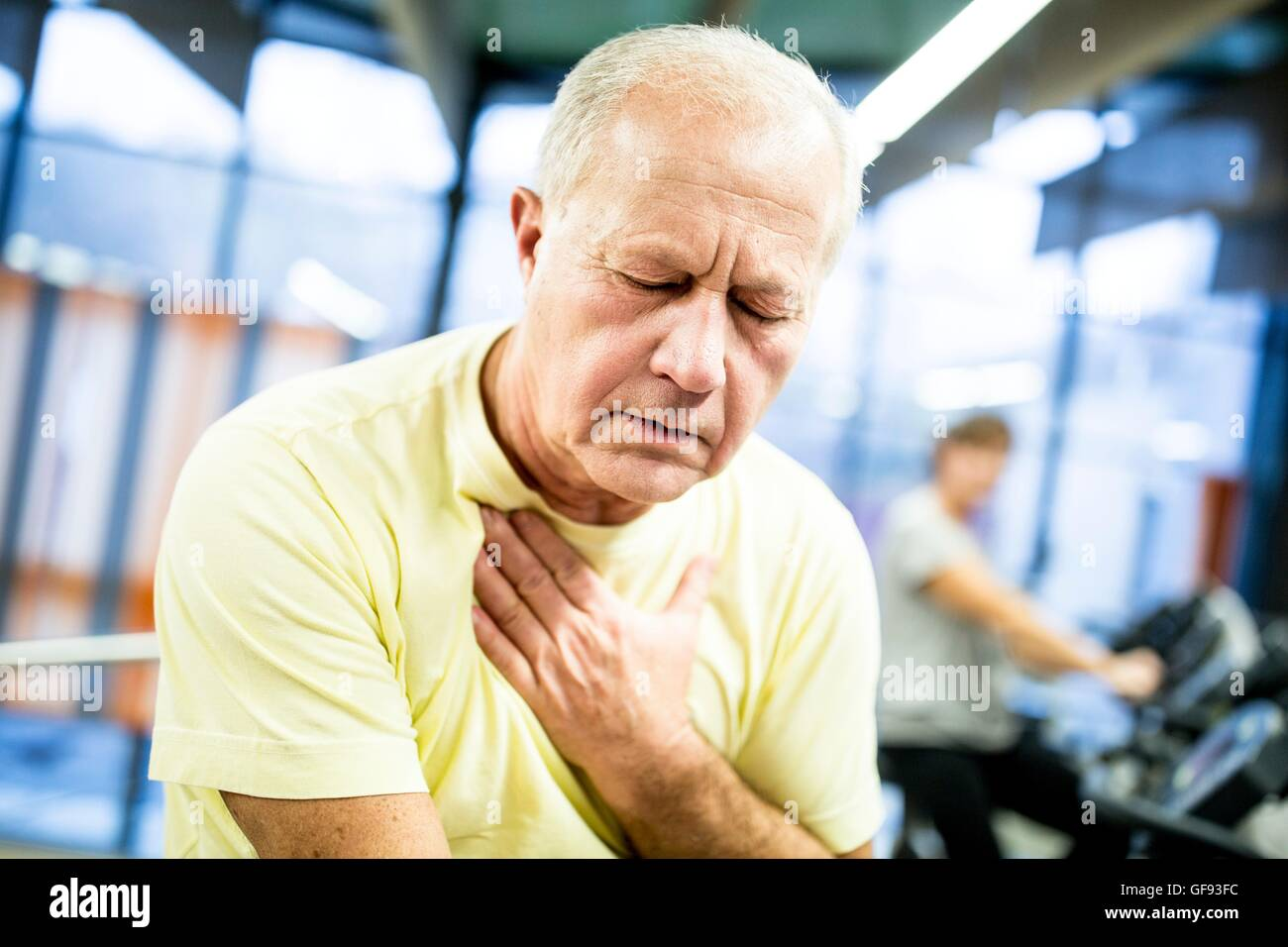 PROPERTY RELEASED. MODEL RELEASED. Exhausted senior man after exercising in gym. - Stock Image
