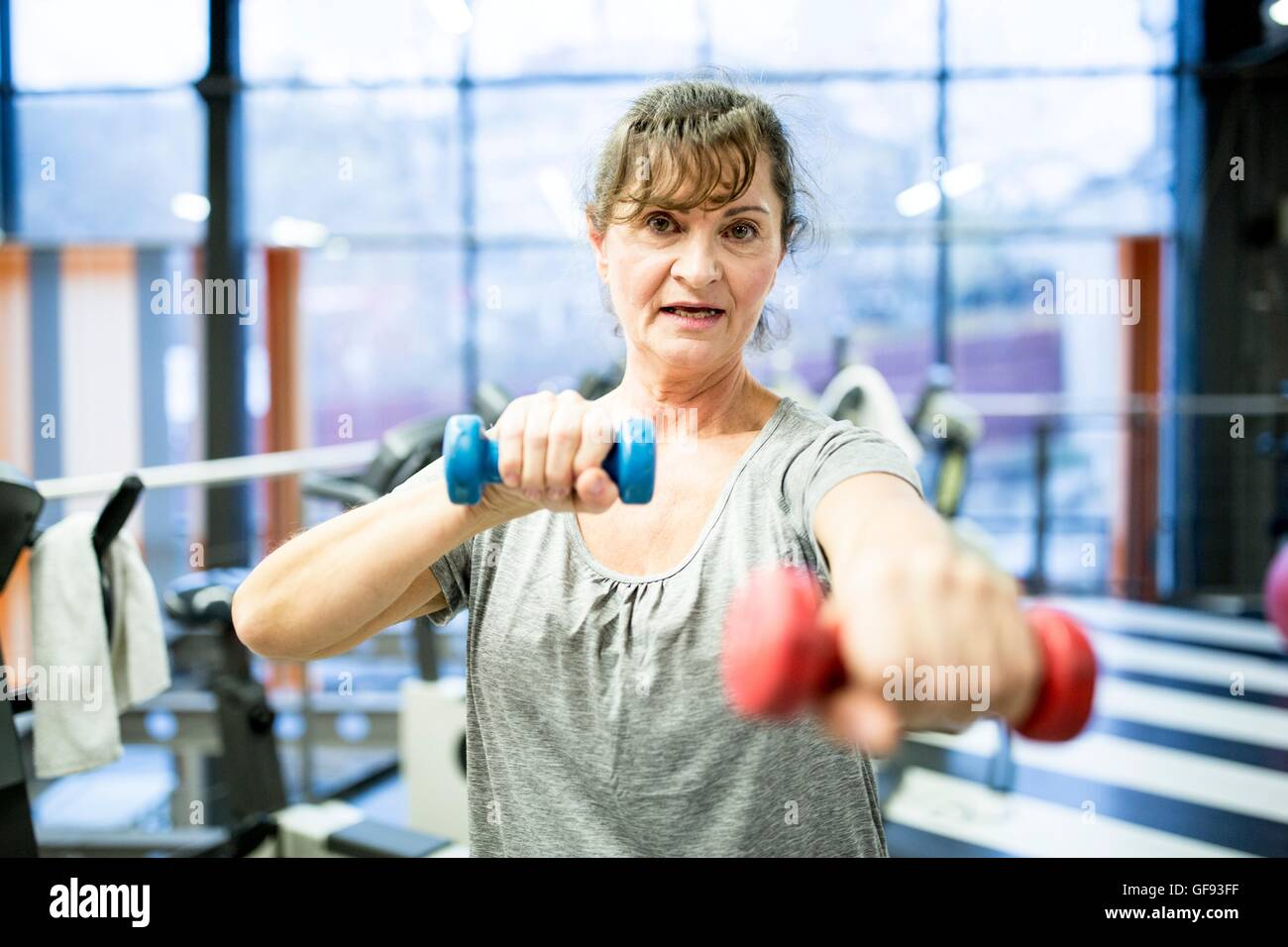 PROPERTY RELEASED. MODEL RELEASED. Portrait senior woman holding dumbbell in gym. - Stock Image