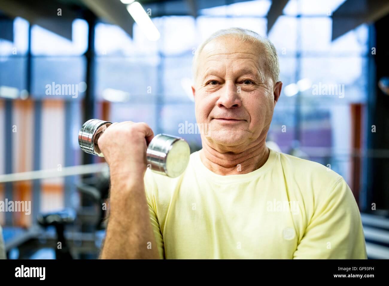 PROPERTY RELEASED. MODEL RELEASED. Portrait senior man holding dumbbell in gym. - Stock Image