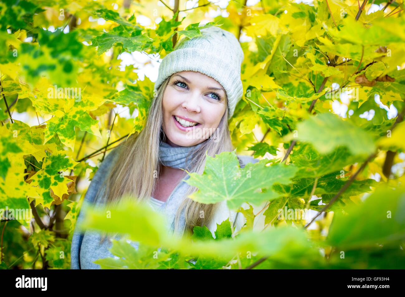 MODEL RELEASED. Young woman smiling while surrounded by autumn leaves. - Stock Image