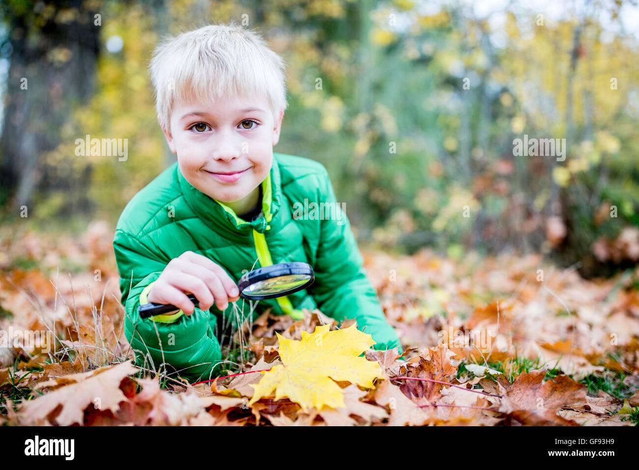 MODEL RELEASED. Boy holding magnifying glass over autumn leaf, smiling, portrait. - Stock Image