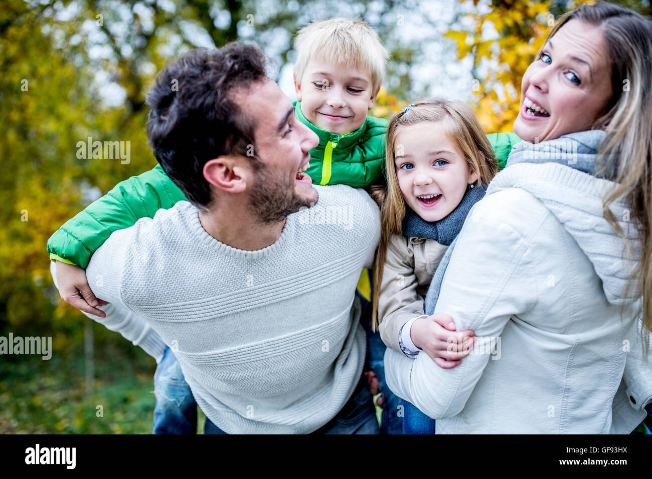 MODEL RELEASED. Parents carrying their children in autumn, laughing. - Stock Image