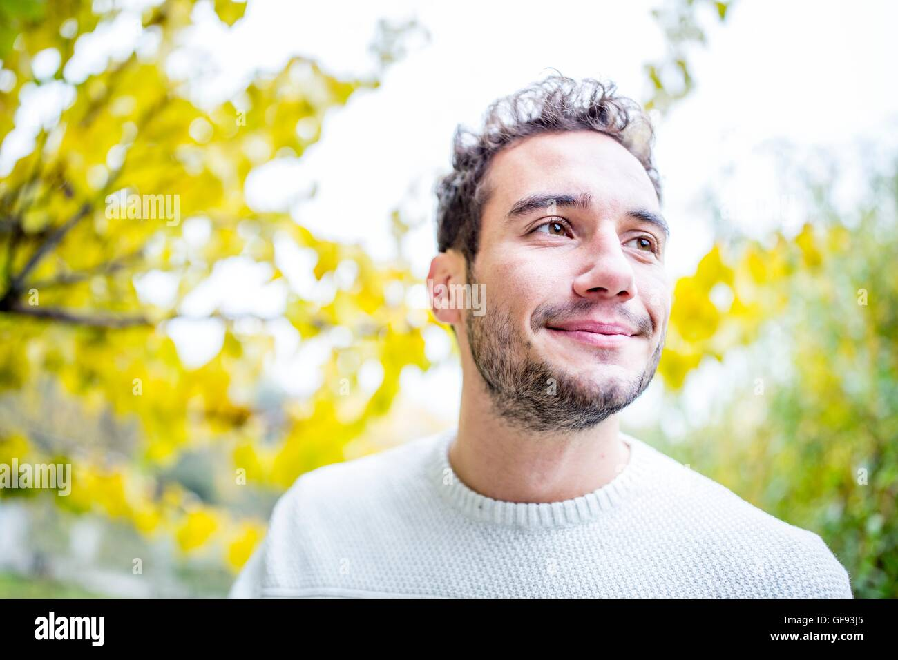 MODEL RELEASED. Young man looking away and smiling, close-up. - Stock Image