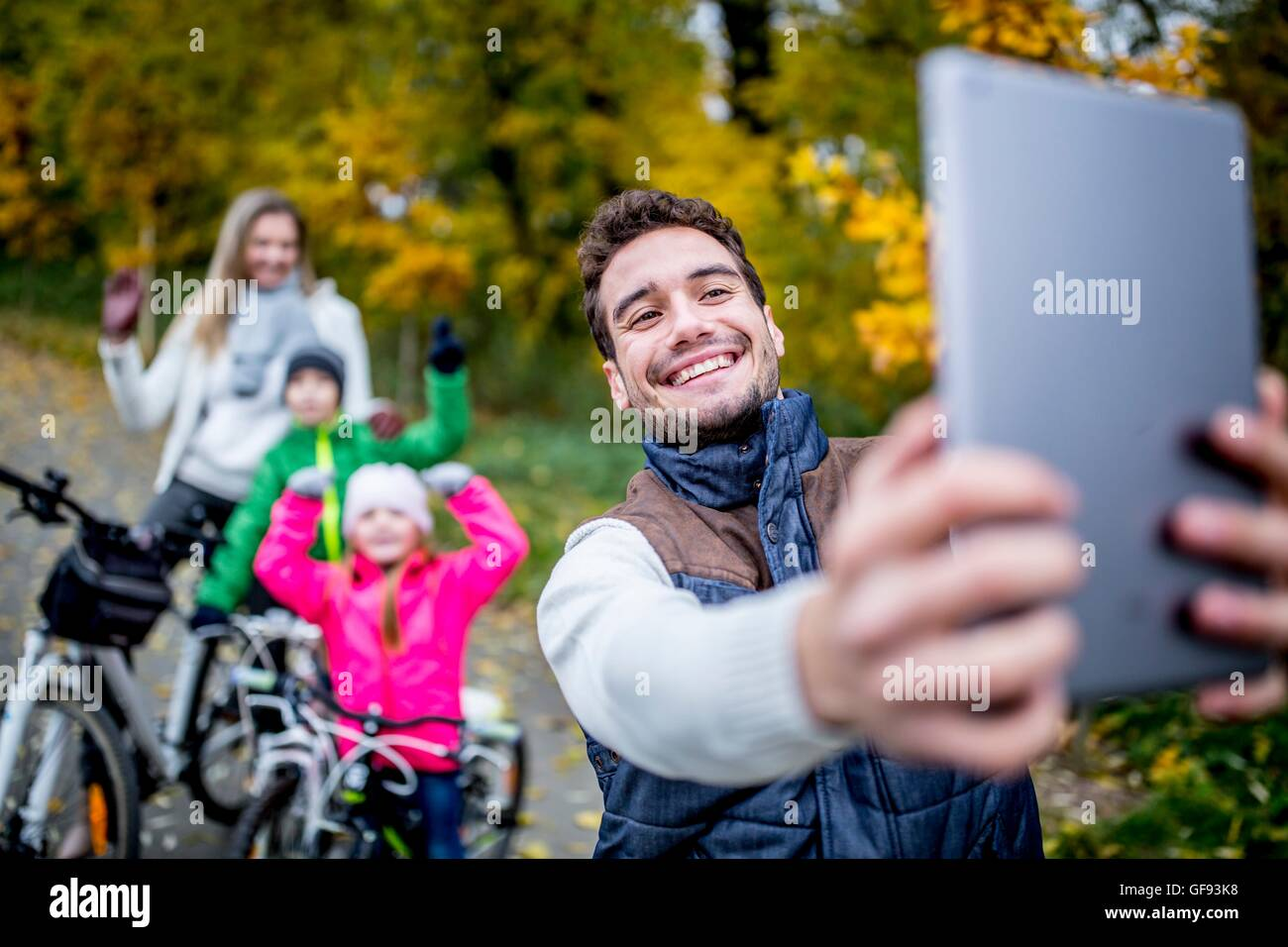 MODEL RELEASED. Smiling man taking photo of family. - Stock Image