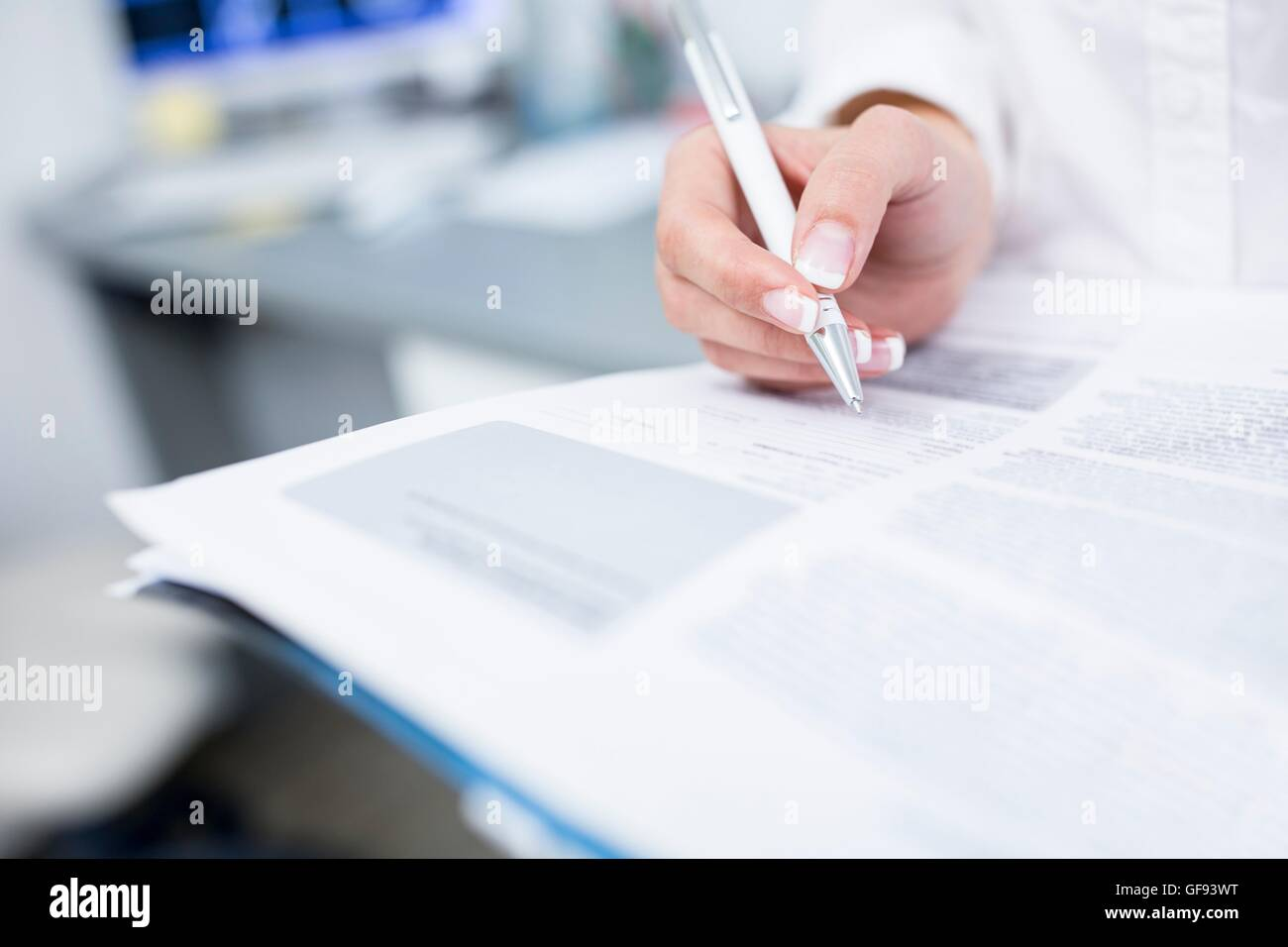 Close-up of dentist's hand writing on file. - Stock Image